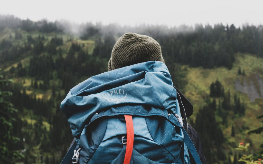 A backpacker is hiking with helpful apps installed on his phone.