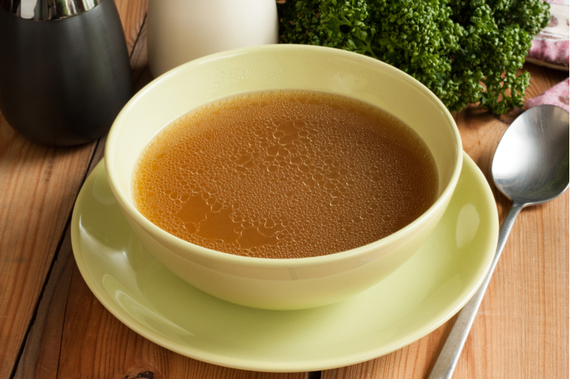 Steaming teacup of bone broth on saucer, at a table with silverware