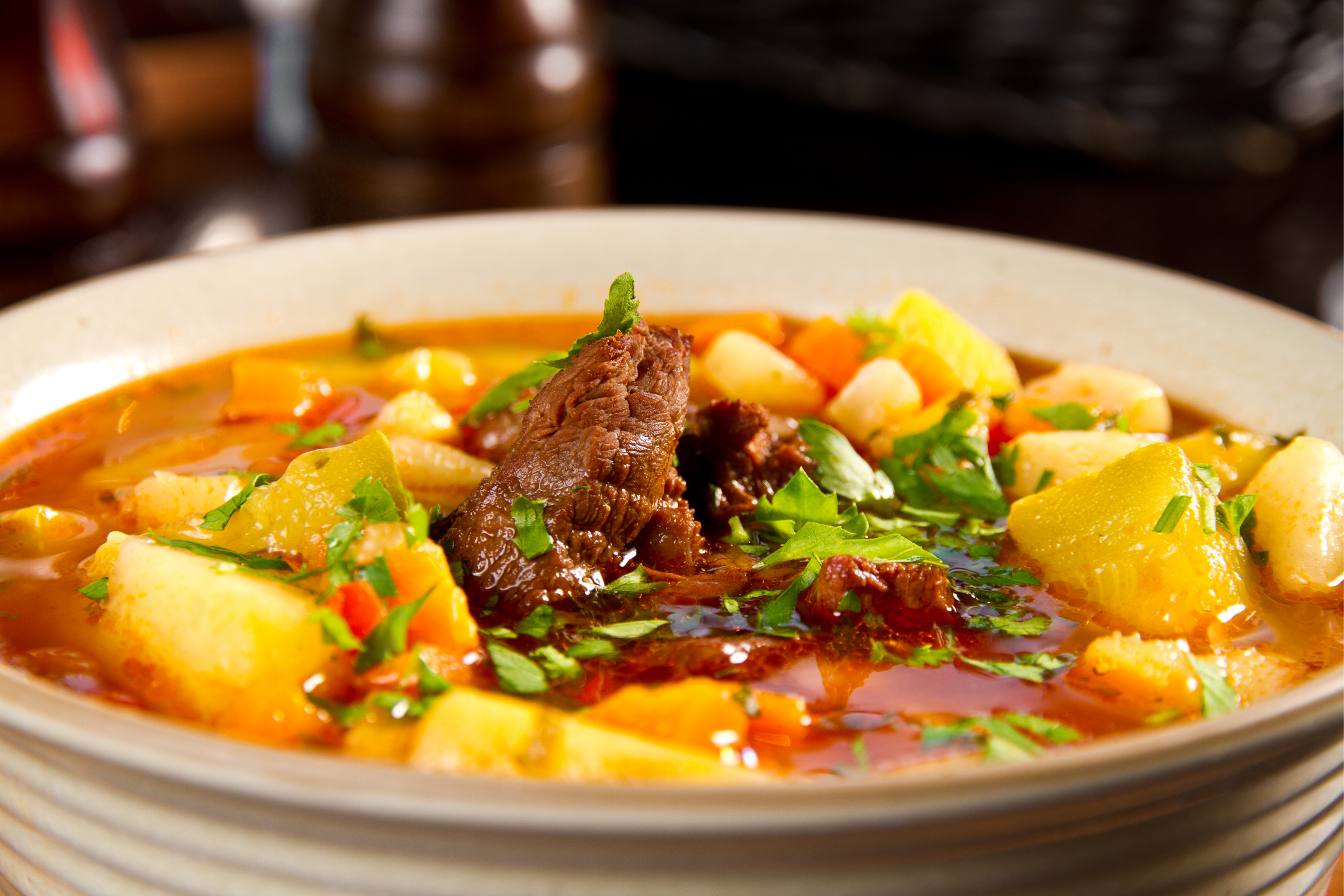 bowl of beef soup with potatoes, carrots, and parsley