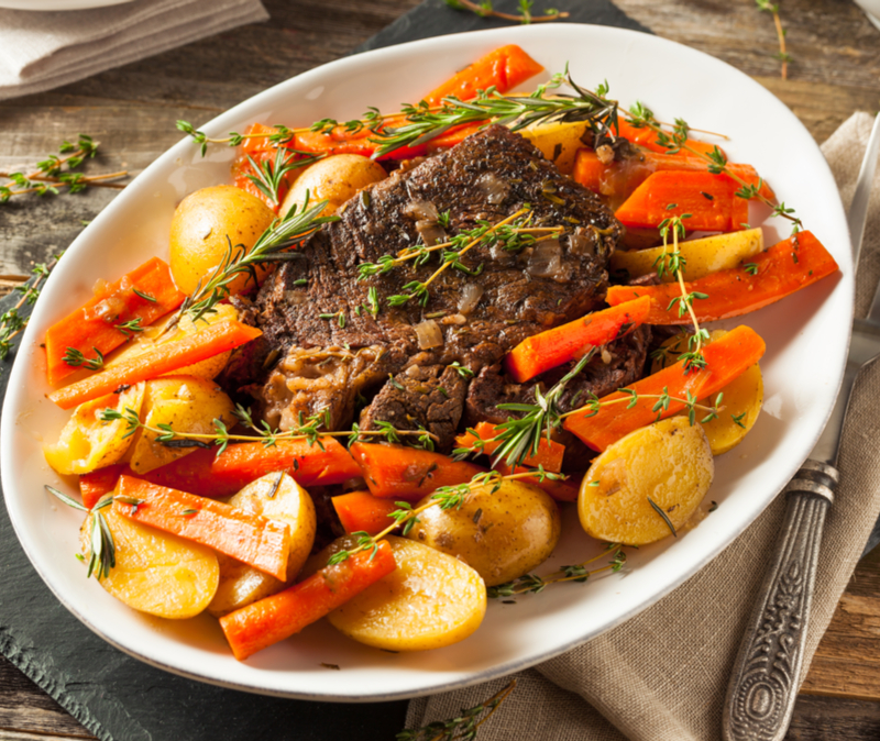 white platter of pot roast surrounded by potatoes and carrots and garnished with thyme