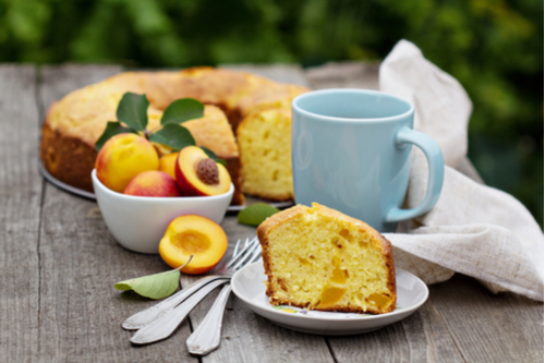 Bowl of peaches, bundt cake, slice of cake, cup of coffee on outdoor wooden table