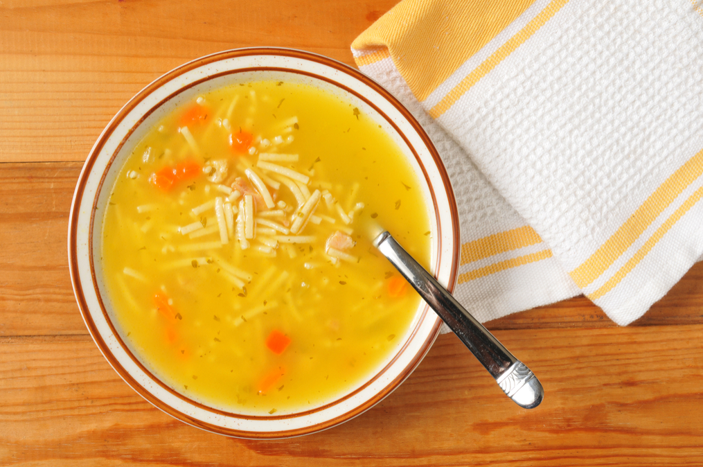 bowl of chicken soup on rustic background, with spoon
