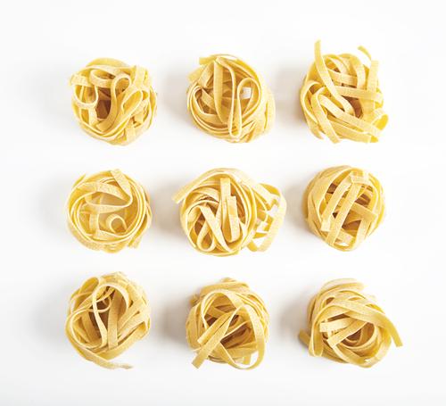 Passover potato starch noodle illustration: dried pasta coils against white backdrop