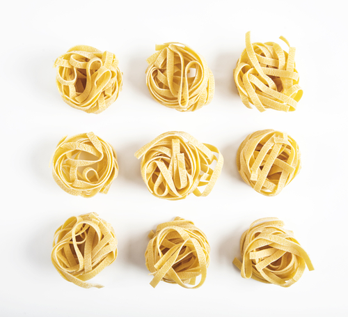 Passover potato starch noodle illustration: dried pasta coils against white backdrop