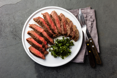 Sliced steak, medium rare, fanned out on white plate with a pile of chopped parsley, as garnish