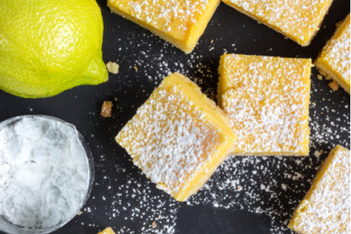 lemon squares and lemon on black background with bowl of powdered sugar