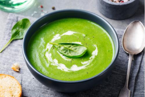 Black bowl holding cream of broccoli soup garnished with basil leaf