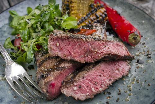 Sliced rare steak on salad