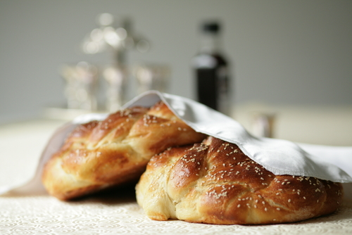 Napkin covered challahs on table set for Shabbat