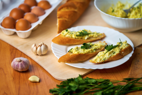 Eggs and onion on a slice of baguette garnished with parsley