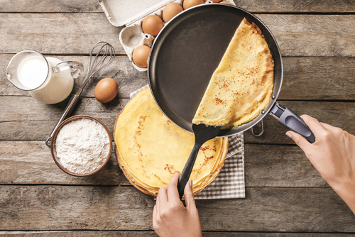 Woman's hand removing crepe from pan with background of crepe ingredients