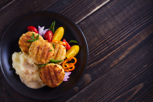 tuna patties on bed of mashed potatoes with colorful vegetables on the side