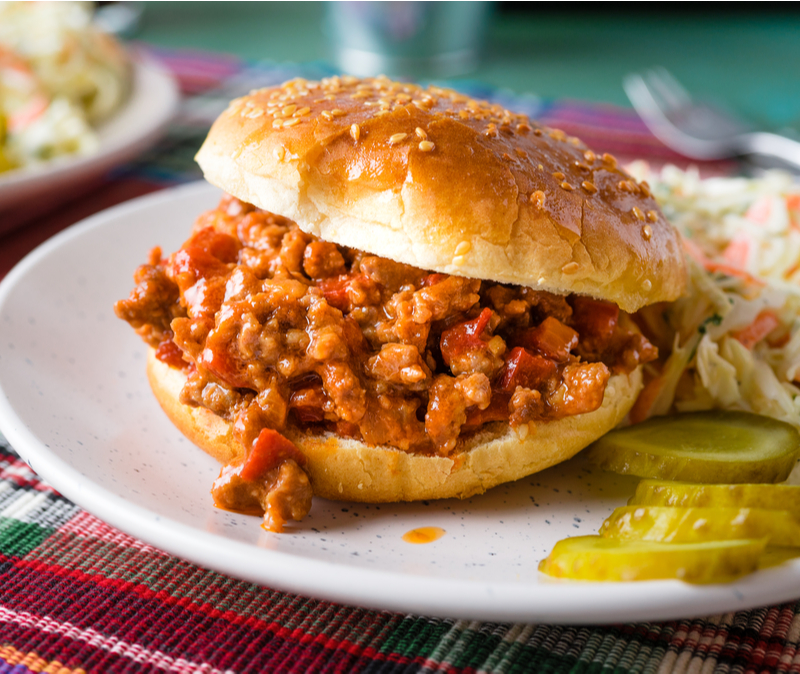 sloppy joe sandwich with pickles and coleslaw on plate