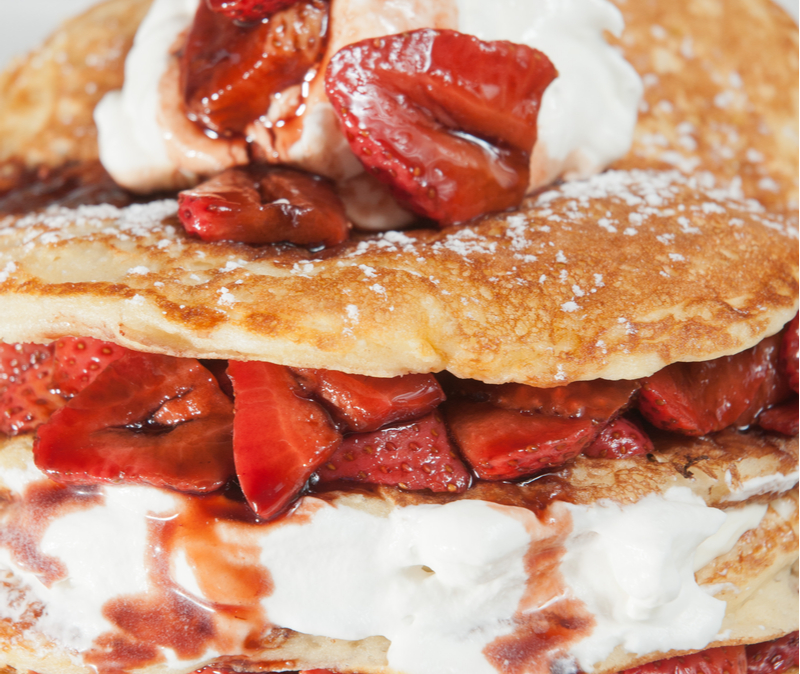 roasted strawberries on pancakes with whipped cream