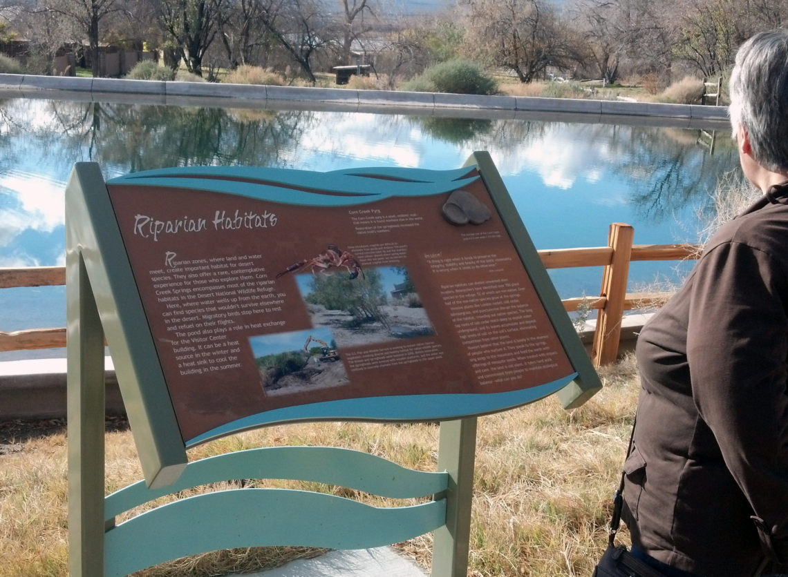 Woman reading trail sign at Corn Creek