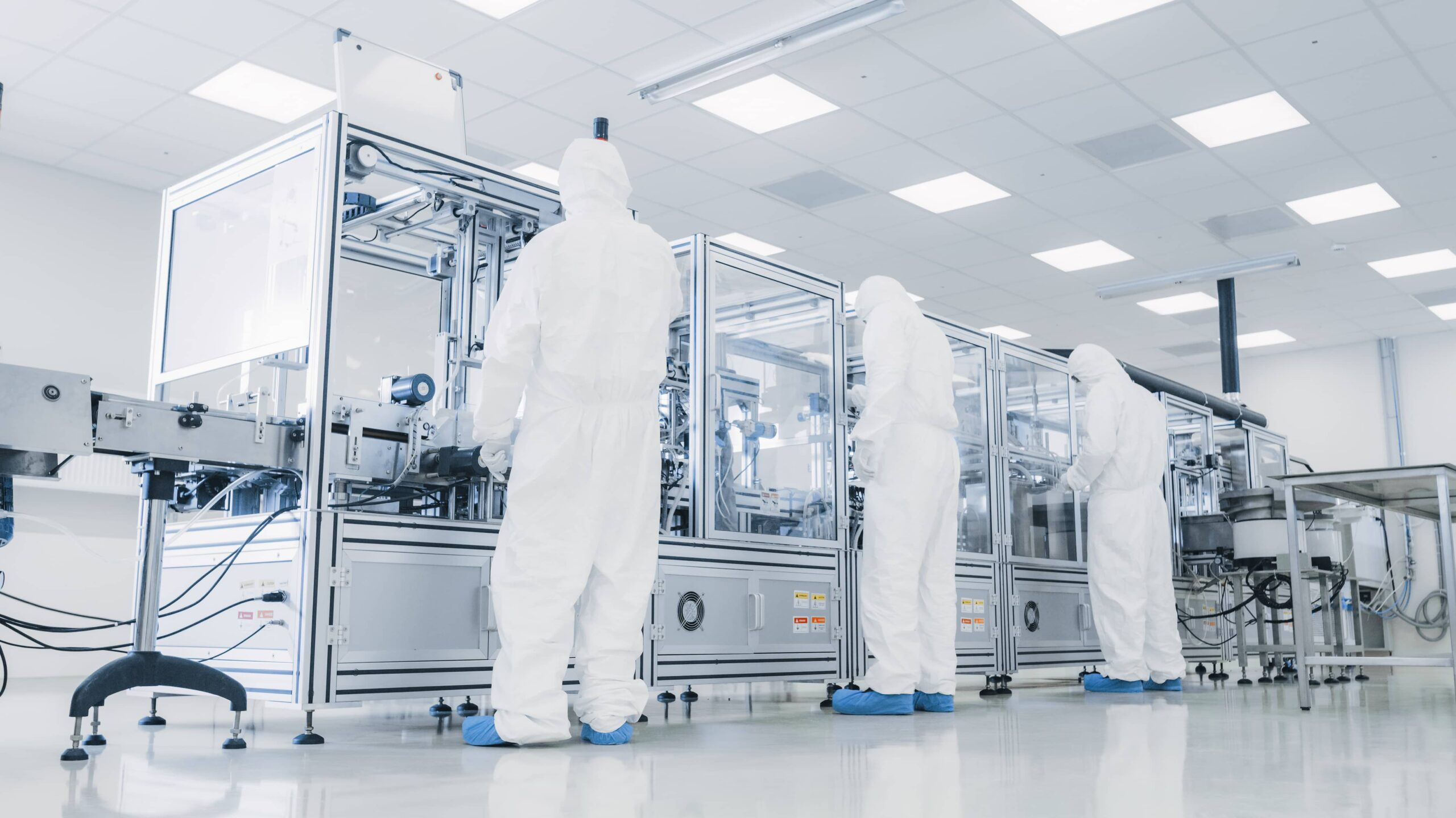 Manufacturing facility team of scientists wearing sterile protective coverall