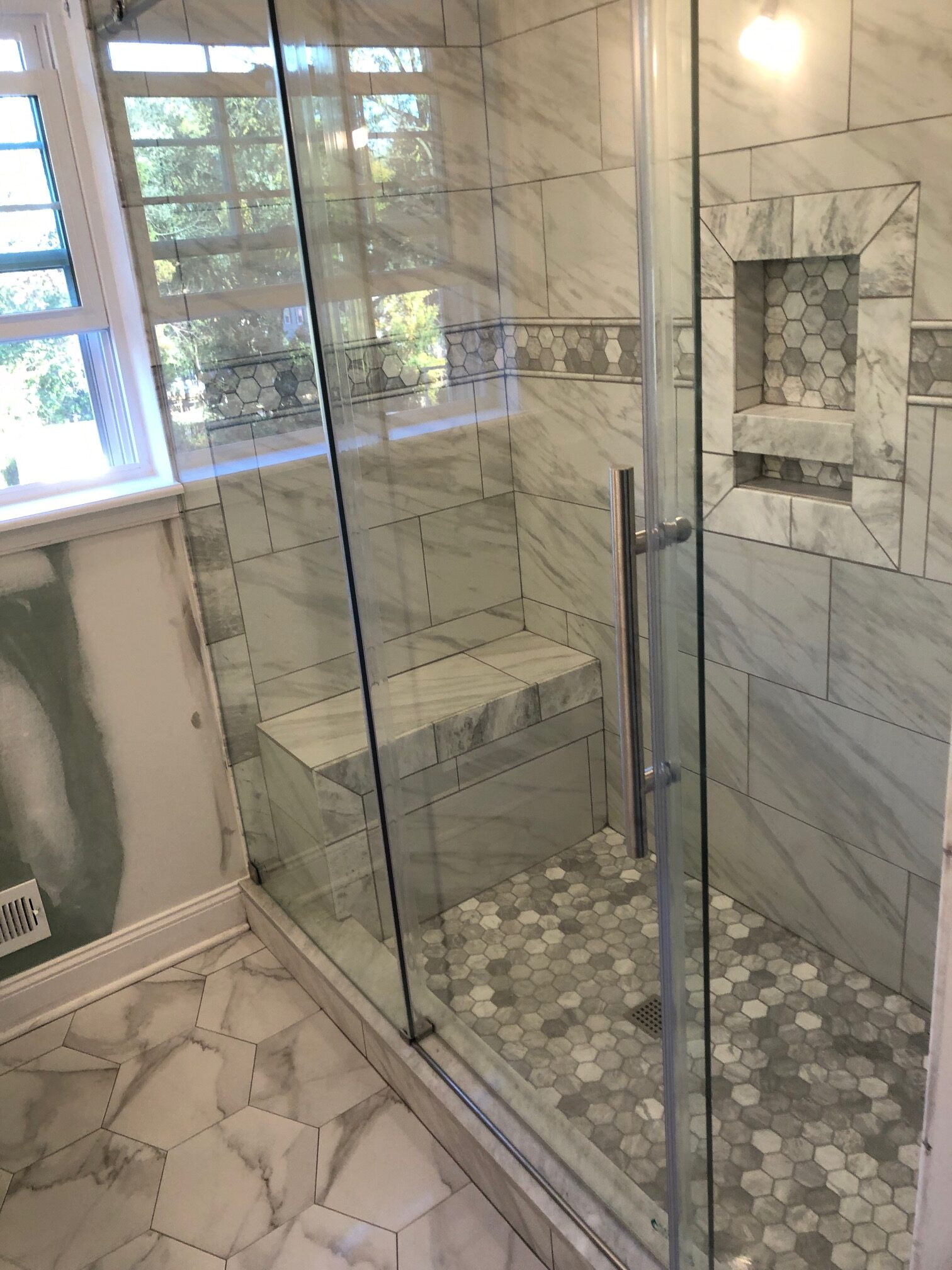 glass shower door with gray and while marble tiles