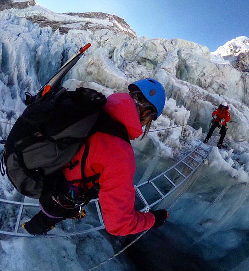 Masha crossing a ladder over a crevasse in Khumbu Icefall, Everest