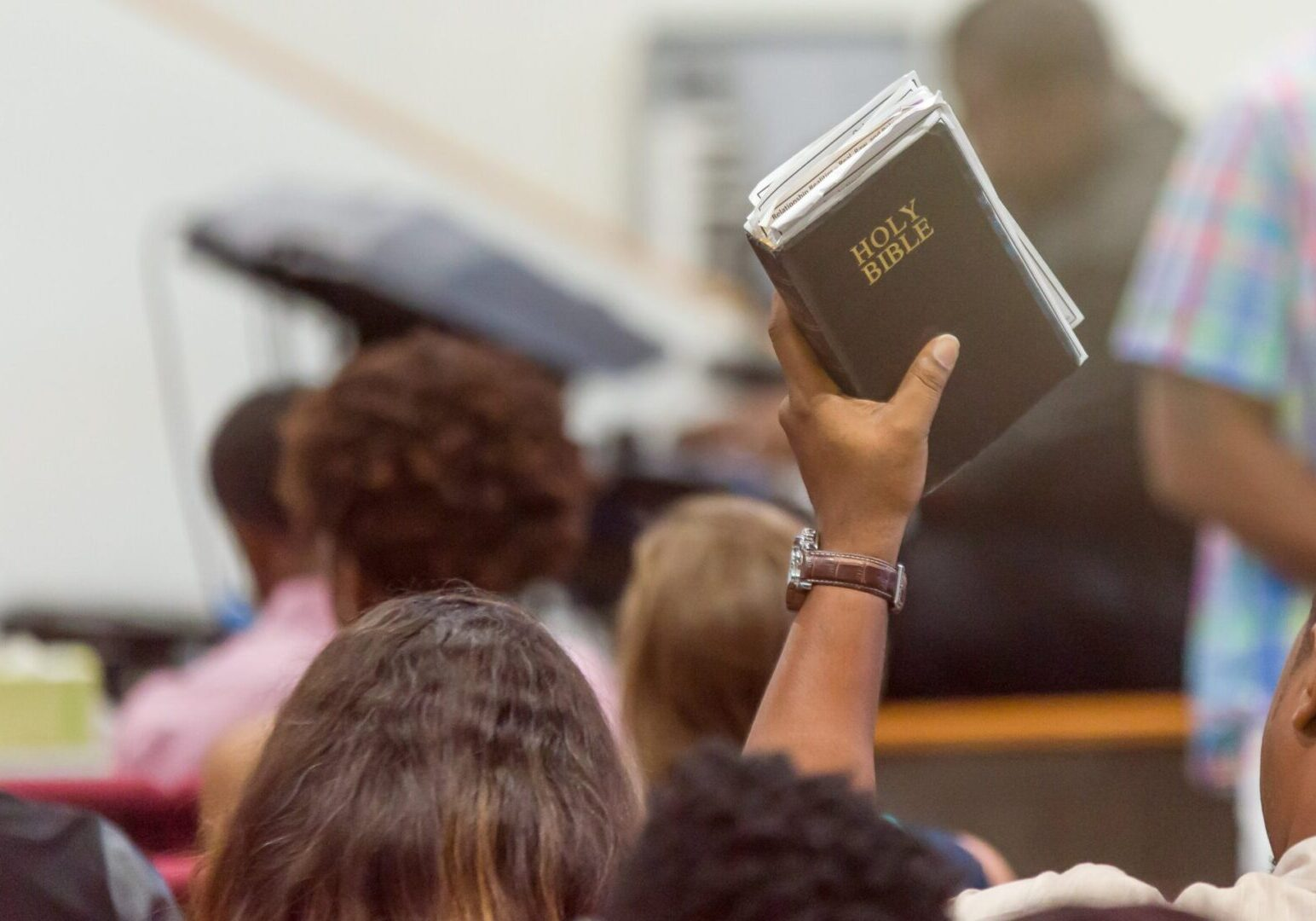 African American Man at Church with a Bible Raised