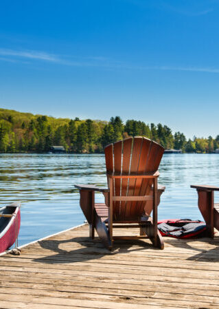 Two Muskoka chairs on a wooden dock overlooking the blue water of a lake in Muskoka, Ontario Canada. A red canoe is tied to the pier and life jackets are visible near the chairs.