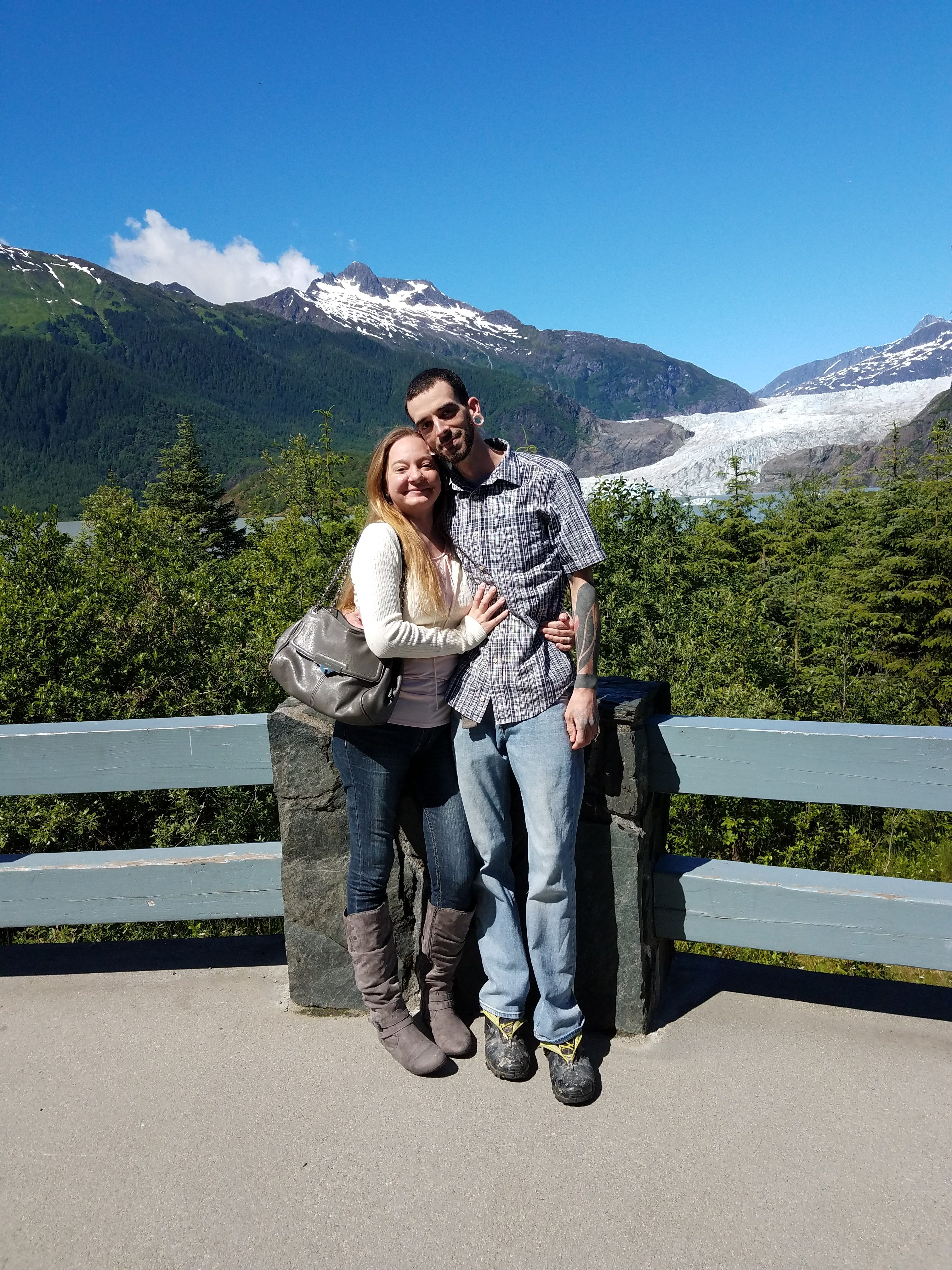 Photo of a couple at the Mendenhall Glacier viewing pavilion with the glacier in the background.