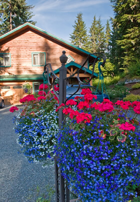 Summer blue and red flower baskets in the foreground.