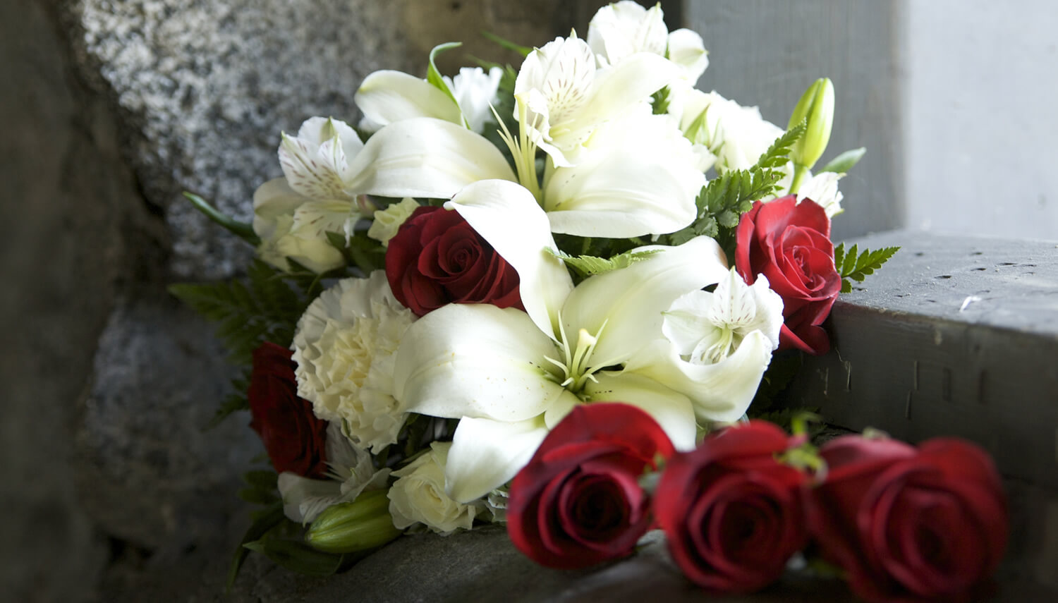 Bridal bouquet with red roses amid with lilies, tiger lilies and carnations and trailing red roses