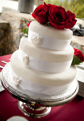 Photo of white, 3-tiered wedding cake topped with crimson roses at a Pearson's Pond wedding.