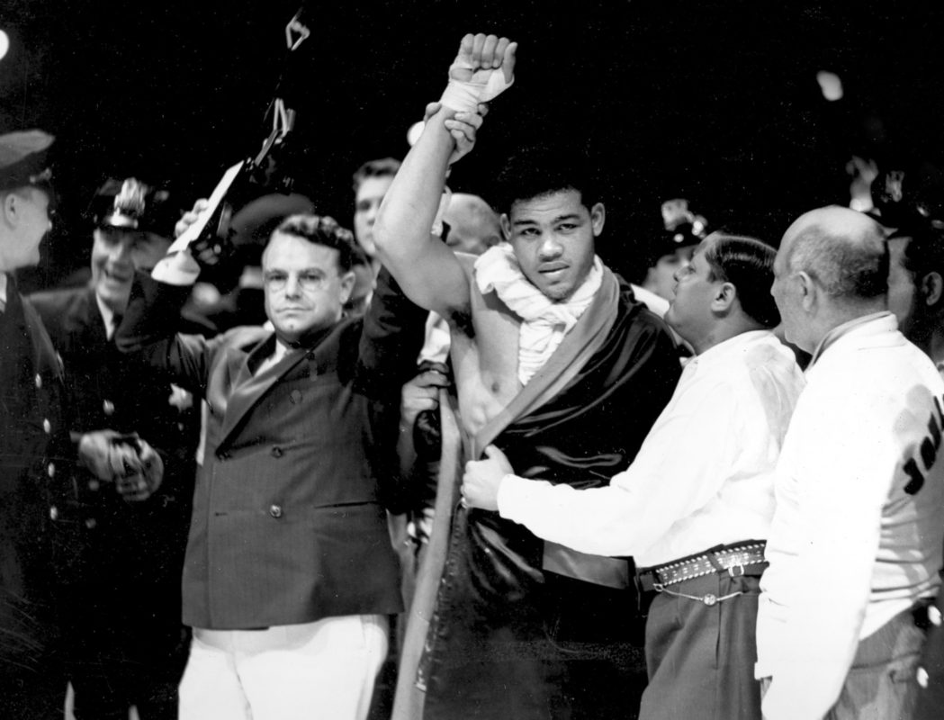 Joe Louis, world heavyweight champion, boxing stadium, black background.