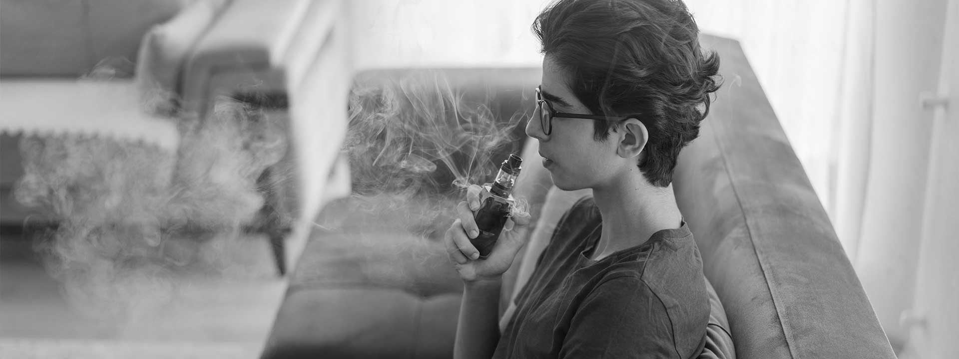 One young teenager vaping at home