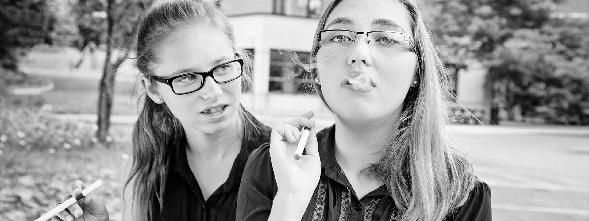 Two young middle school girls trying vape