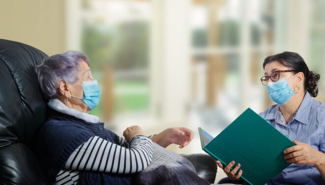The kind woman talks to her and reads books. Both wear face protective masks and keep their distance due to the coronavirus epidemic.
