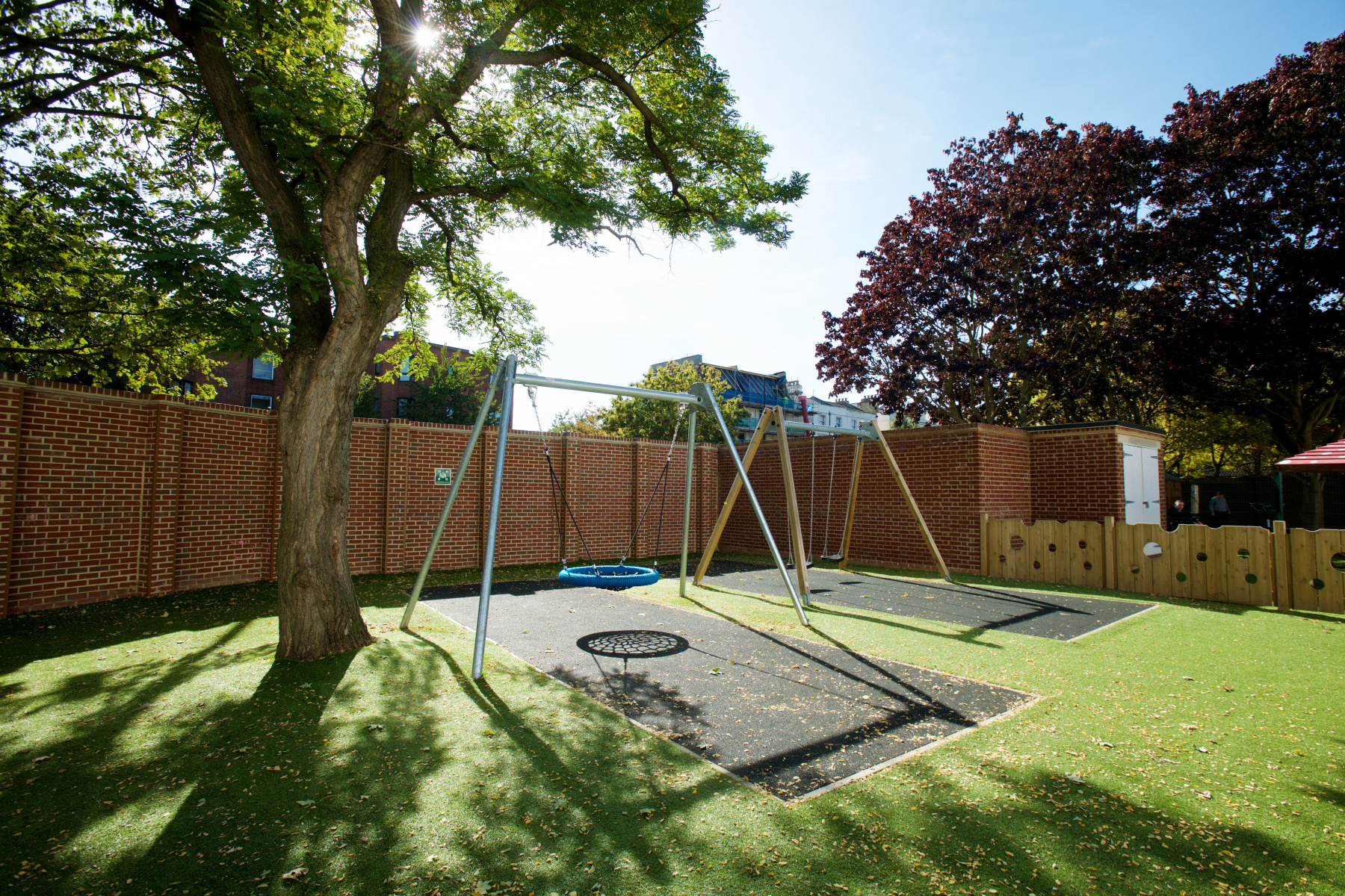 Large modern swing in a walled garden with a large tree in the sunshine