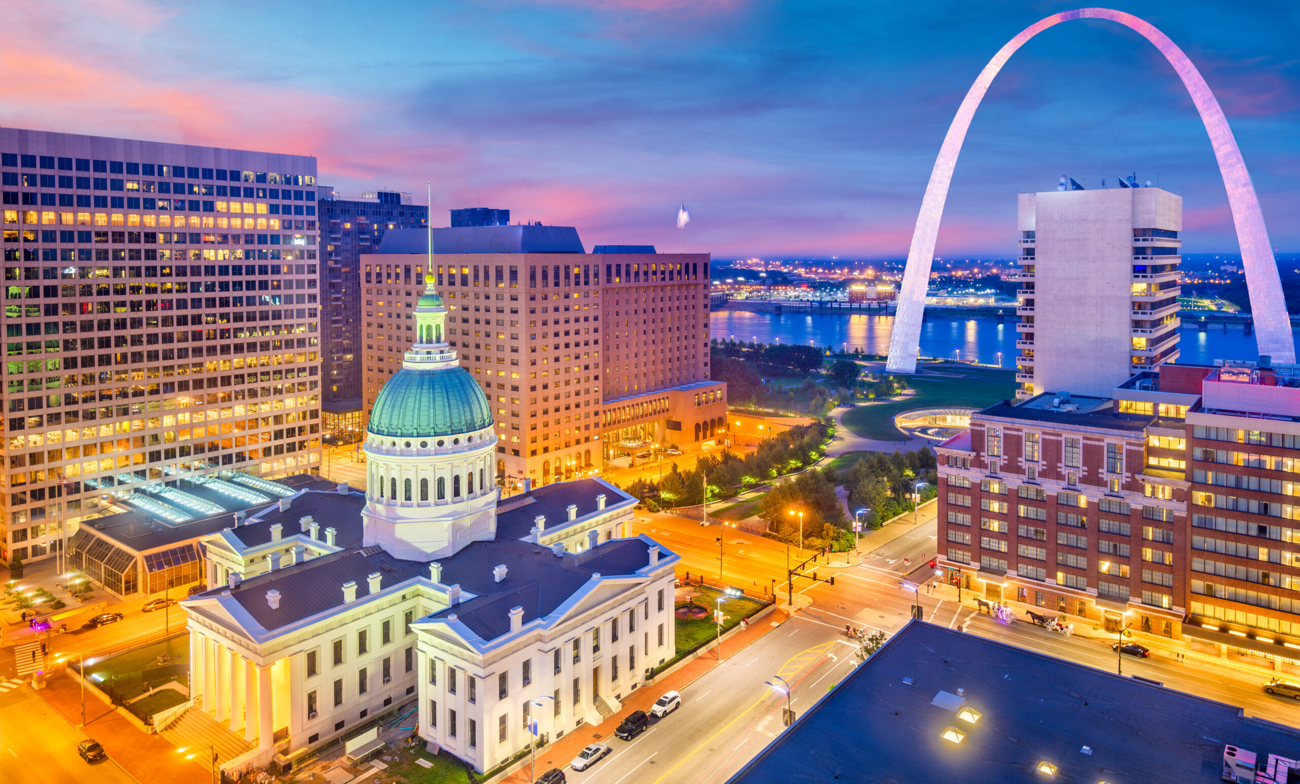 St. Louis, Missouri, USA downtown cityscape with the arch and courthouse at dusk.