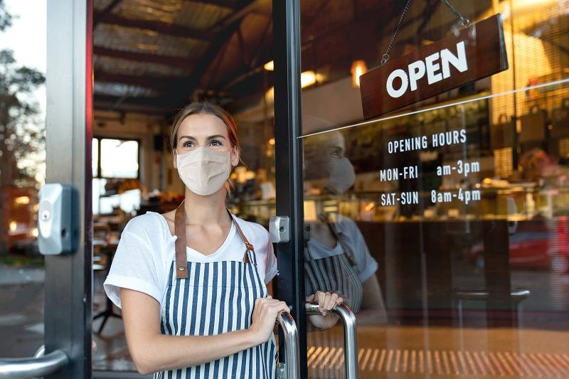 Happy-business-owner-opening-the-door-at-a-cafe-wearing-a-facemask-cm