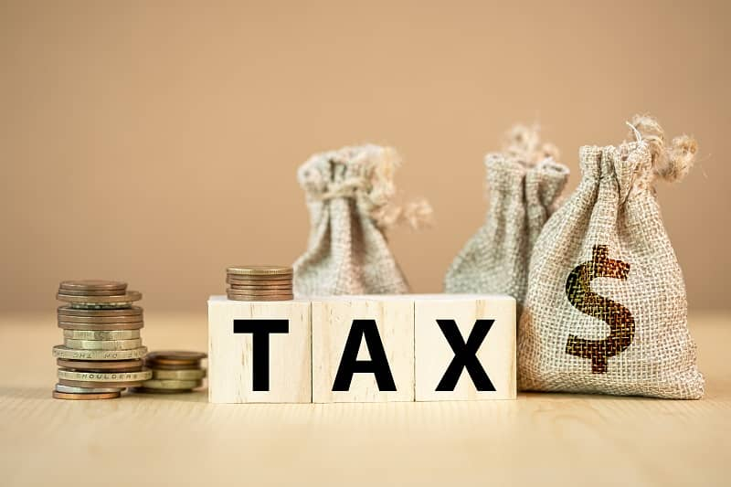 Tax wording on wooden cubes with US dollar coins and bag.-cm (1)