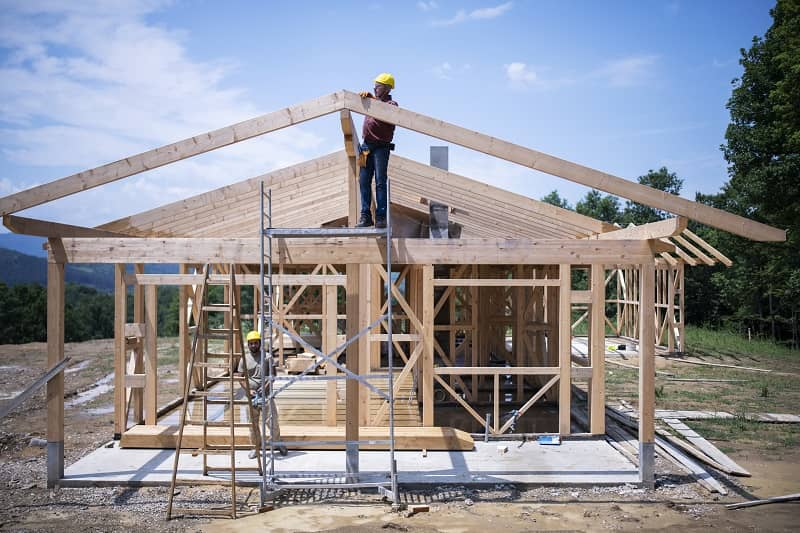 Construction Workers Working On Wooden Roof Of House.-cm