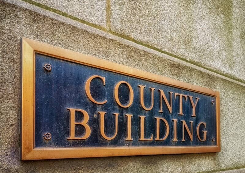 Exterior sign that reads County Building in brass letters.-cm