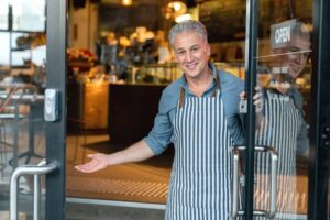 Business owner at the door of a cafe welcoming customers-cm