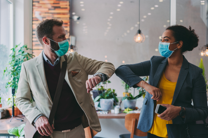 Business people greeting during COVID-19 pandemic with elbow bump