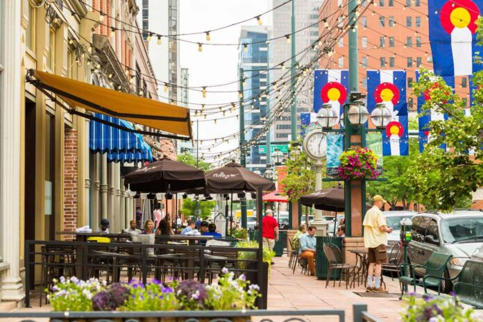 Sidewalk in downtown Denver with covered restaurant patios and Colorado state flags.