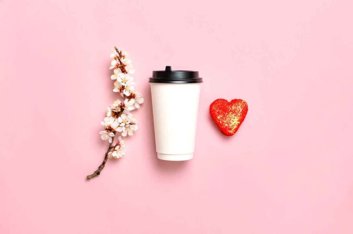 Sprig of flowers, white to go coffee cup, and red heart on pink background.