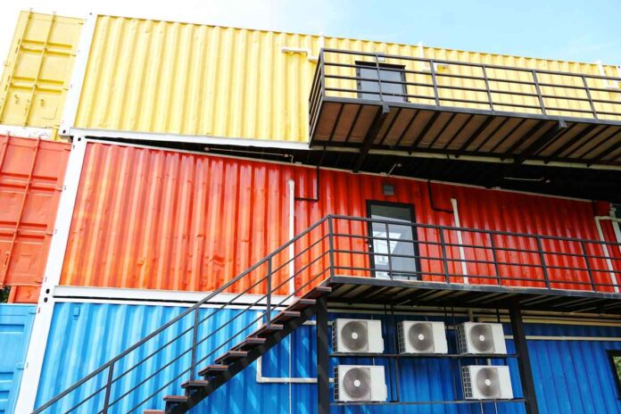 A stack of blue, yellow, and red commercial shipping container that have had windows, doors, and stairs added.