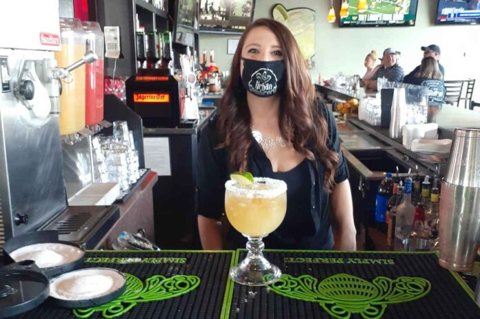Female bartender wearing a face mask and standing behind the bar with a mixed drink in a large glass goblet.
