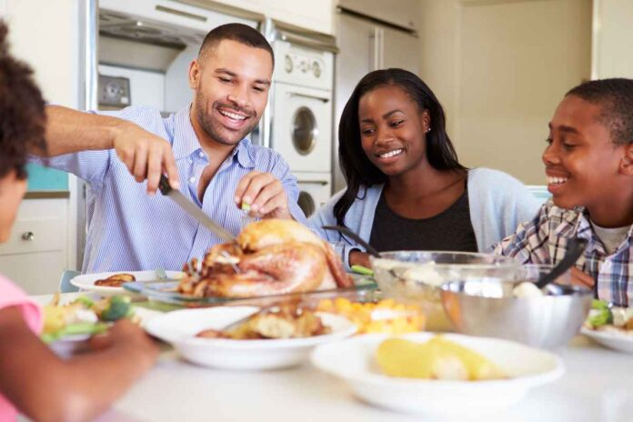 Smiling African-American family at dinner table around roast turkey.