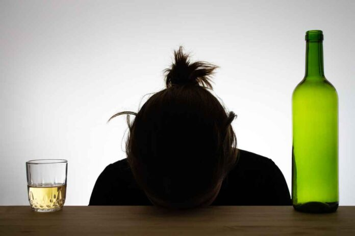 Silhouette of woman with her forehead resting on a table, a glass filled with amber-colored liquid on her left and an empty wine bottle on her right.