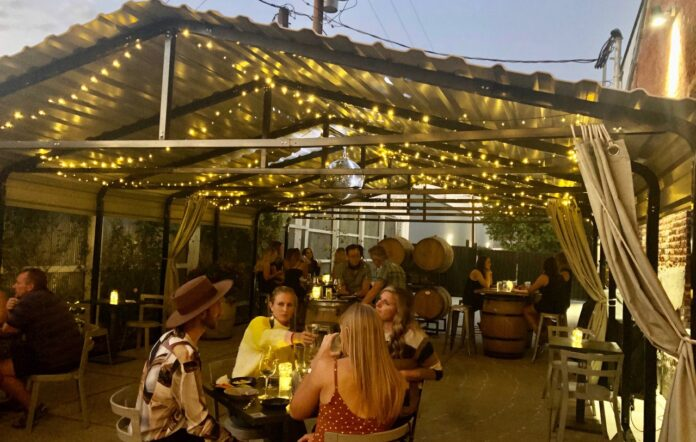 Small groups of people seated at tables outside underneath a carport. The structure is lit with string lights and a disco ball.