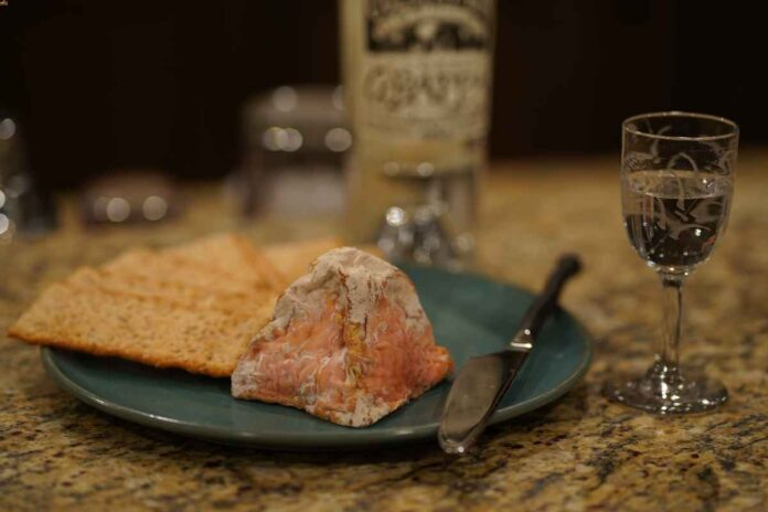 Crackers and a piece of pink-ish cheese on a blue plate with a cordial glass next to it.