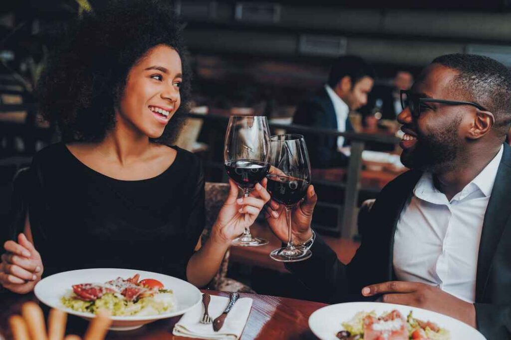 Black man and woman in a restaurant eating dinner and toasting with glasses of red wine.