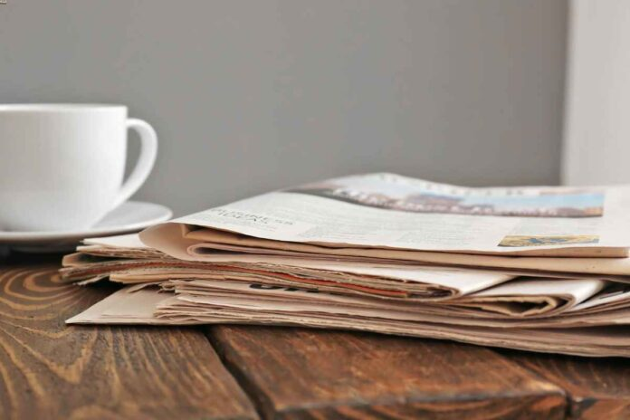 Pile of newspapers with cup of tea on wooden table.